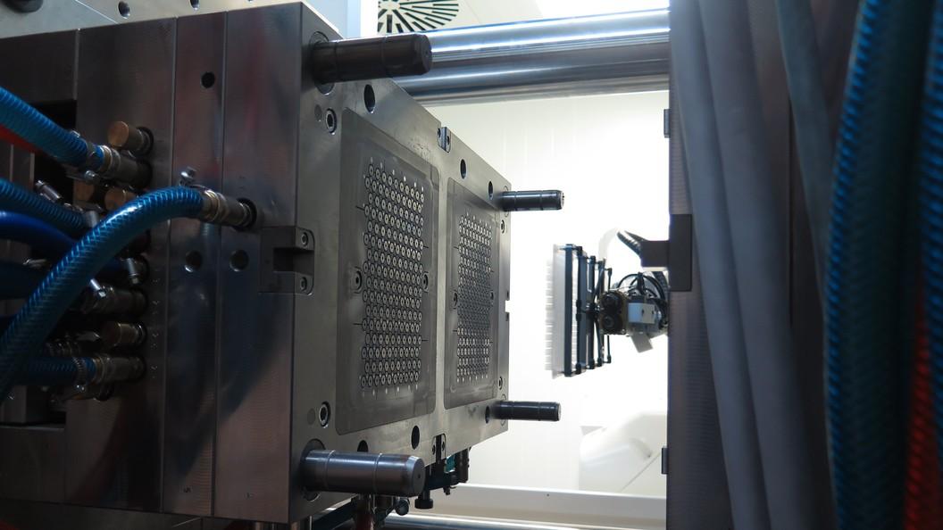 Zwei Roboter entnehmen bei Verwendung eines Etagenwerkzeugs parallel die Spritzgussteile