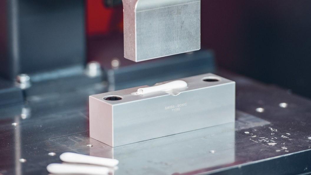 Zwei identische Bauteile werden mittels Ultraschallzu einer Schutzkappe verschweisst.