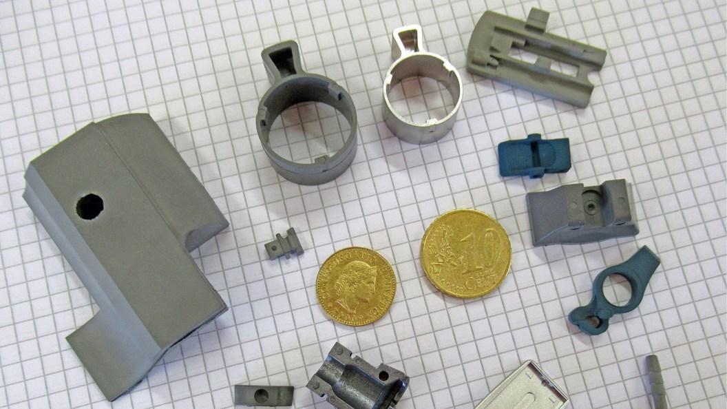 Eine Auswahl typischer MIM-Teile in verschiedenen Fertigungsstadien vom Grünteil über das Braunteil
