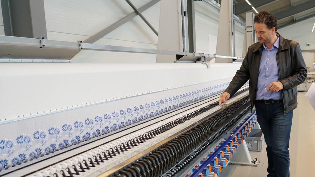 LÄSSER-Verkäufer Markus Eberle erklärt die Funktionsweise der fertigen Stickmaschine