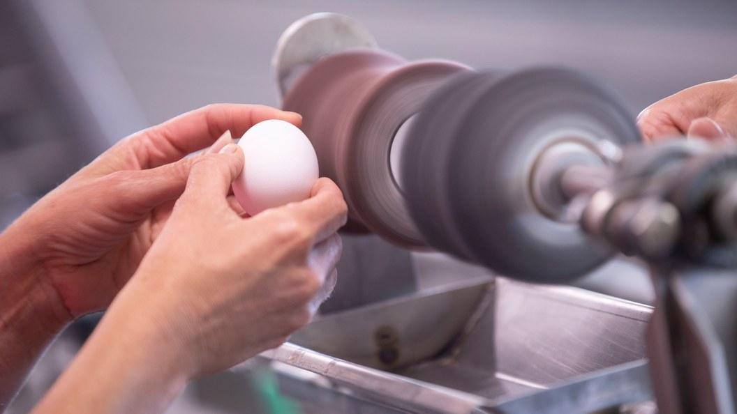 Das Ei wird mit einer oder zwei Händen an den Bürstenwalzen gereinigt.