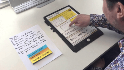 """An example of an app's layouts drawn on paper. A common practice for testing paper prototypes is to have one person play """"computer,"""" switching the sketches around according to user choices."""