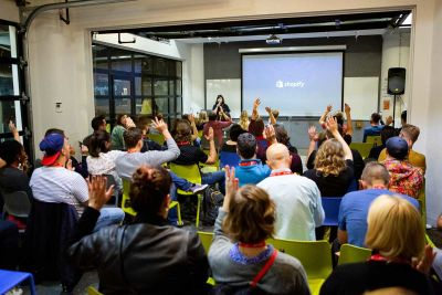 People watching a talk and raising their hands