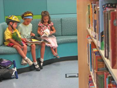 Three children sit reading books individually