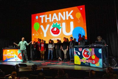 A large group of people on stage under a slide that says Thank You.