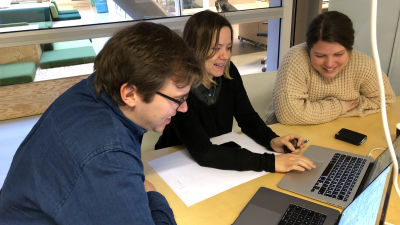 Three people are smiling and sitting next to each other around a computer. From left to right, they are Dag-Inge (CTO), Ida (CPO) and Ingvild (Sr. Engineer).
