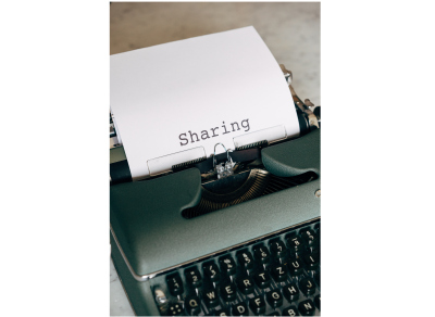 """A manual typewriter is displayed. A white sheet of paper is in the typewriter with the word """"Sharing"""" typed out on the page"""
