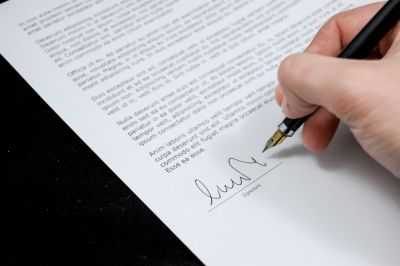Hand writing signature on a piece of paper