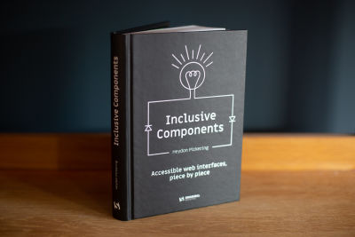 A picture of a black-and-white book cover standing on a wooden surface abd tilted to the side titled Inclusive Components, Accessible web interfaces, piece by piece, written by Heydon Pickering