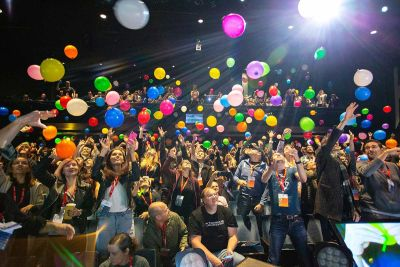 An audience throwing colored balloons into the air, taken from the stage