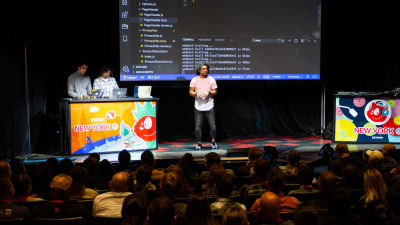 A photo of Dan Mall standing on stage explaining code shown on the screen behind him