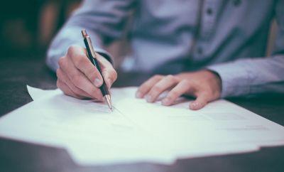 man holding pen on paper