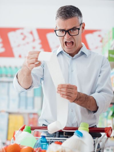 Man screaming and looking stressed while holding a long receipt