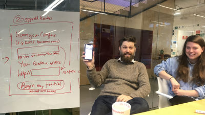 A whiteboard is showing rough sketches of a sign-up form. A man (Svein) and a woman (Ingvild) are smiling and discussing.