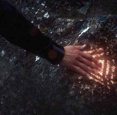 Man touching big rock with shining symbol