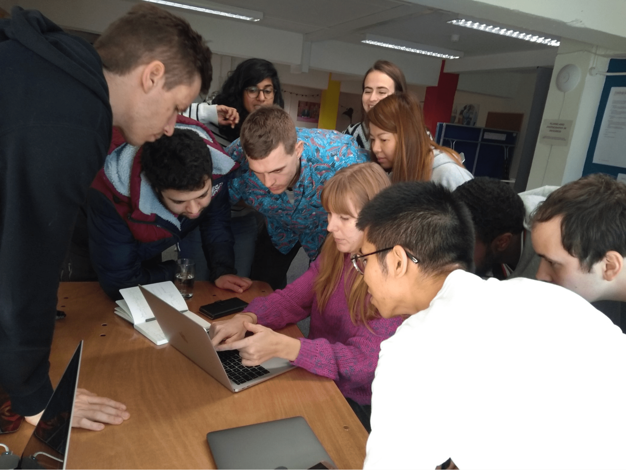 Ten developers huddled around a laptop using mob programming to solve a problem together.