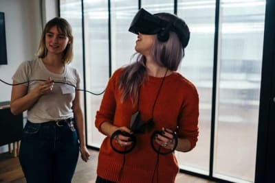 Girl with VR head-mounted display and controllers in her hands and girl holding wire