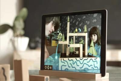 Tablet mirroring kids playing game KOSKI, enhanced with imaginative plants, figures and waterfall