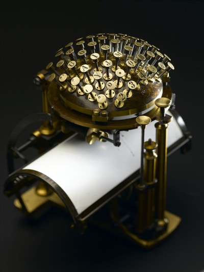 The Hansen Writing Ball has brass colored keys arranged as if on the top half of a ball, with a curved sheet of paper resting under them.