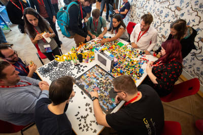 Overhead shot of people doing jigsaw puzzles and building lego