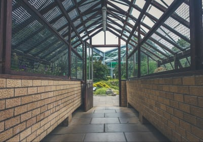 A long hallway leads to an open door revealing a greenhouse full of plants