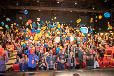 Conference attendees standing up throwing balloons