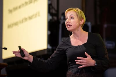 A woman presenting on stage