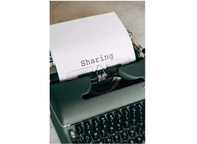 "A manual typewriter is displayed. A white sheet of paper is in the typewriter with the word ""Sharing"" typed out on the page"