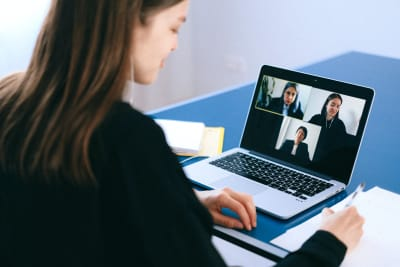 Woman sitting at laptop on video call with three others