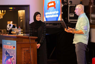 A man and woman on stage, the woman behind a lectern