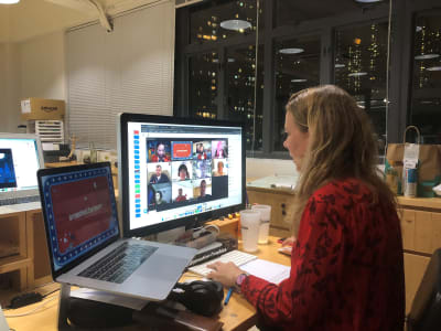 A woman sitting at two screens, one has lots of people on video