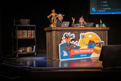 Chris Coyier and Brad Frost sitting at a desk on stage talking