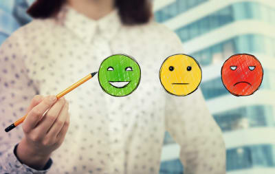 Image of a woman holding a pencil to a green smiley face. There is also a yellow face and mad red face