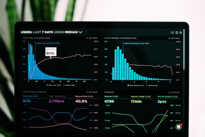 A photo of a laptop screen displaying 4 charts showing line and bar graphs comparing different user metrics