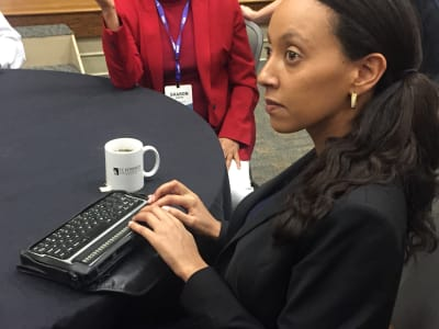 Haben Girma sits at a conference table and uses her braille reader.