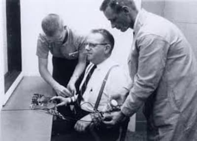 A black and white photo of two researchers attaching shock probes to a research participant