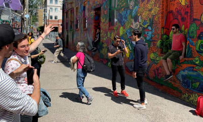 People in a street taking photos of graffiti