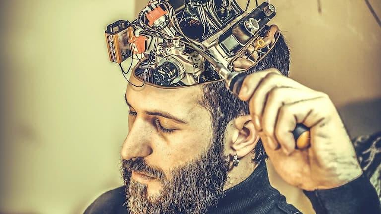otwarta głowa zmechanizmem zamiast mózgu, wktórej osoba majstruje śrubokrętem