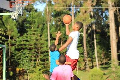 Estudiantes jugando baloncesto en la hora de deporte.