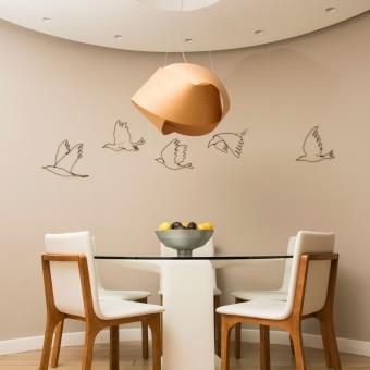 פינת אוכל עגולה על רקע של קיר עגול. פסלי ציפורים על הקיר ומנורה מקליפת עץ.