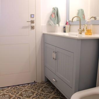 חדר אמבטיה עם רצפה מאוירת וארון רחצה בתכלת.