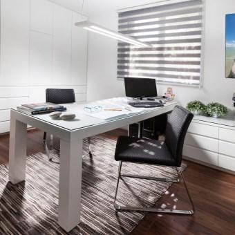 חדר עבודה עם שולחן במרכז החדר ופינת עבודה למכשור וניירת.