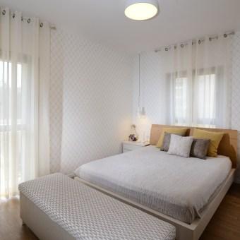 לחדר השינה נבחרו גוונים רכים, והקיר חופה בטפט מעוינים על-זמני.