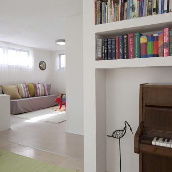 חדר המשפחה מופרד במפלס מהסלון, ובמעבר אליו תוכננה פינה עבור ספריה והפסנתר.