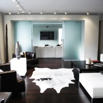 שטיח לבן מעור במרכז הסלון השובר את הפרקט החום כהה