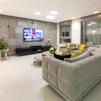 הספה המרכזית חוזרת על המוטיב העיצובי של הקיר מאוחרי הטלויזיה