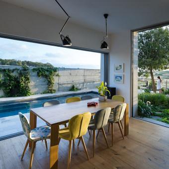 פינת אוכל עם ויטרינות משני כיווני אויר, כיסאות צהובים לצד שולחן מעץ מלא