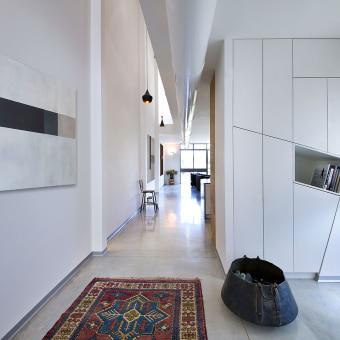 מסדרון עם שטיח פרסי ארוך ותמונת קיר מודרנית