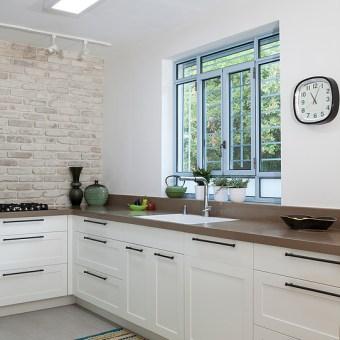 מטבח לבן עם שיש כהה על רקע קיר לבנים
