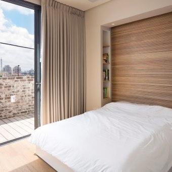 שקע בקיר המיועד למיטה עם מדפים לספרים ותאורה מובנת ברקע פסי עץ לרוחב